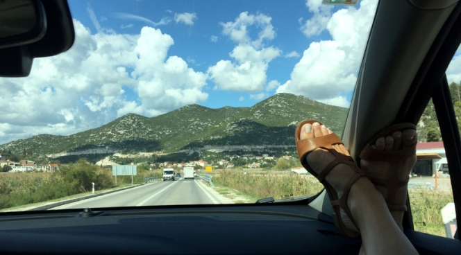 Feet in a car window driving throughout Croatia